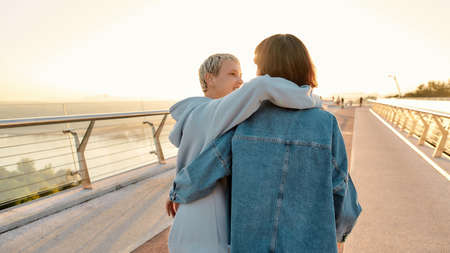 Lesbian couple standing on the bridge, embracing each other while admiring the sunrise together. Homosexuality, LGBT and love concept