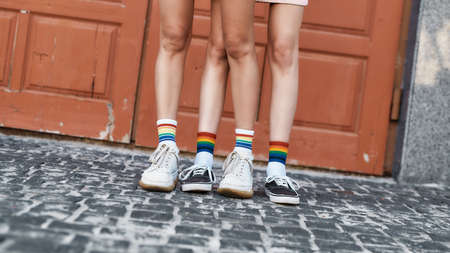 Close up of legs of young girls wearing rainbow colored socks, standing together in front of the door outdoors. LGBT, Sexual freedom concept