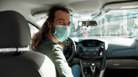 Man taxi driver talking to a passenger while steering the car during coronavirus pandemic wearing sterile medical mask, Social distance and health care concept