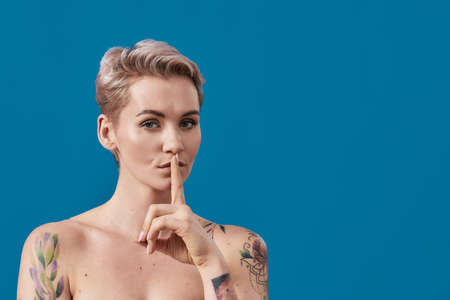 Portrait of a young attractive half naked tattooed woman with perfect skin looking at camera, holding a finger on her lips isolated over blue background