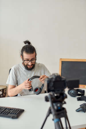 Male technology blogger in glasses holding and showing headphones while recording video blog or vlog about new gadgets at home studio 免版税图像