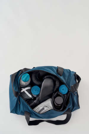 Training and workout equipment. Top view of a sports bag with boxing gloves, hand wraps, clothing, bottle of water and etc isolated on grey background 免版税图像 - 155185618