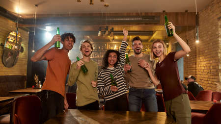 Loud and Proud. Happy friends standing in the bar watching sports match on TV together, drinking beer and celebrating victory. People, leisure, friendship and entertainment concept