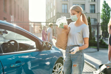 Young woman in medical mask and protective gloves standing near her blue car, unlocking door alarm system while holding grocery bag