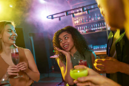 A group of friends, young women and men chatting while having fun, drinking cocktails, spending time in the night club