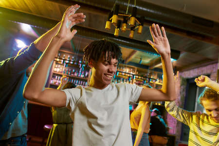 Cheerful mixed race young man having fun, dancing with friends at party in the bar 免版税图像 - 155185628