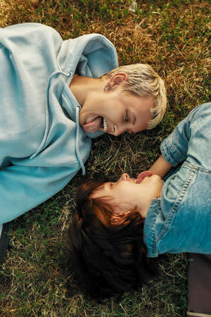 Top view of happy lesbian couple smiling at each other, showing tongues while lying on the grass in summer park, girls in love spending time together outdoors 免版税图像 - 155185631