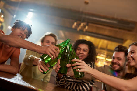 A group of happy friends in the bar clinking bottles while drinking beer together. People, leisure, friendship and entertainment concept 免版税图像