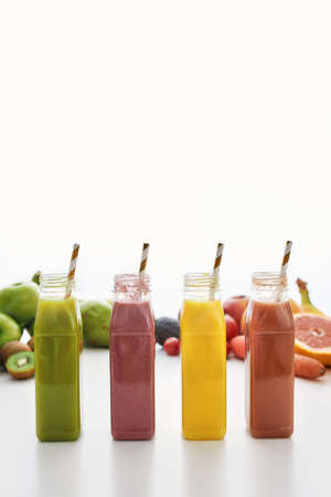 Composition of healthy detox juices and smoothies in bottles with paper straws, Various colorful fruits and vegetables isolated over white background 免版税图像 - 155185643