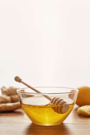 Close up of honey in a bowl with dipper, fresh ginger, lemon, on the wooden table over white background, Preparation of cold and flu remedy cure drink 免版税图像 - 155185653