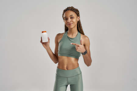 Fitness supplements. Young athletic mixed race woman in sportswear pointing at the bottle with vitamins, capsules or pills while standing isolated over grey background 免版税图像 - 155185663