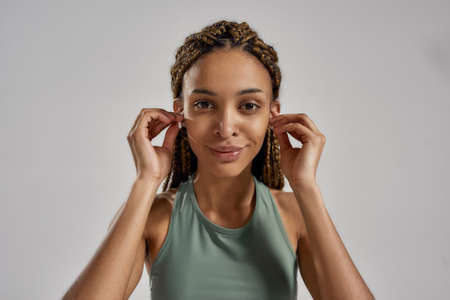 Portrait of young african fitness woman wearing wireless earbuds, looking at camera and smiling while standing isolated over grey background Stockfoto
