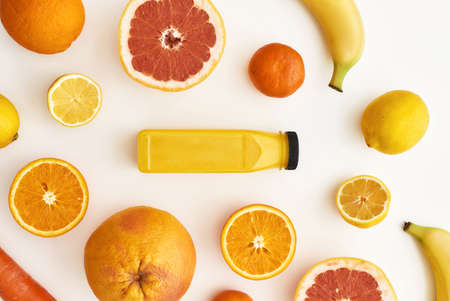 Top view composition of various yellow and orange fruits with bottle of healthy detox juice or smoothie isolated over white background