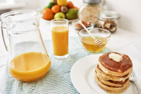 A jug and a glass of orange juice, honey in a bowl, a stack of pancakes and various fruits served for breakfast on the table 免版税图像 - 155185681