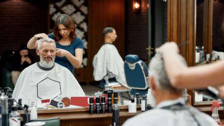 Handsome mature bearded man sitting in barbershop chair while female barber making haircut for him. Barbershop