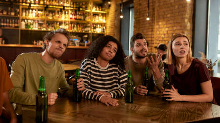 Friends looking disappointed while watching sports match on TV together, drinking beer and cheering for team in the bar. People, leisure, friendship and entertainment concept 免版税图像 - 155185709