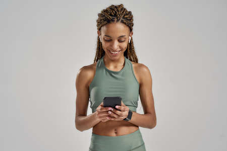 Young positive mixed race fitness woman texting message on smartphone and smiling while standing in studio isolated over grey background, resting after workout
