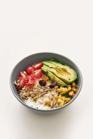 Close up of healthy vegetable bowl lunch with sliced cherry tomatoes, avocado, corn, rice and seeds isolated over white background 免版税图像