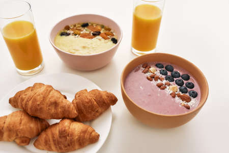 Close up of smoothie bowl with fresh berries, orange juice in glass and croissants on a plate isolated over white background