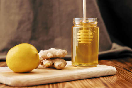 Close up of fresh ginger, lemon, honey in a jar with dipper on the wooden board, Preparation of cold and flu remedy cure drink