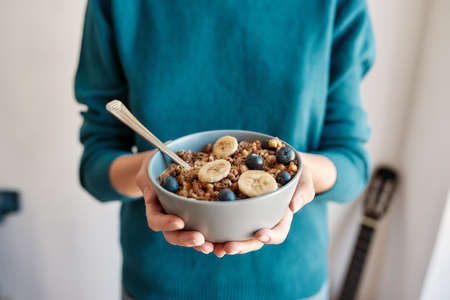 Close up of hands of woman holding homemade granola in a plate with nuts, honey, blueberries, banana and other natural ingredients, Focus on a bowl 免版税图像