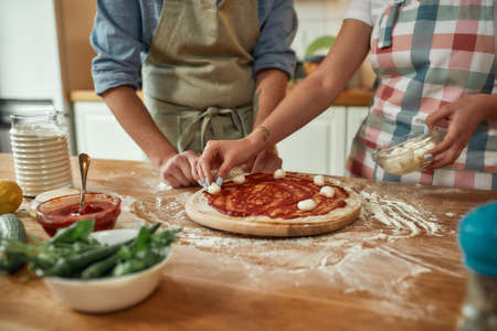 For cheesy taste. Cropped shot of couple making pizza together at home. Man in apron adding, applying tomato sauce on the dough while woman adding mozzarella cheese. Hobby, lifestyle 免版税图像 - 155192839