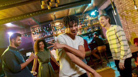 Cheerful mixed race young man posing at camera, dancing at party in the bar. Friends celebrating, having fun in the background 免版税图像 - 155194043
