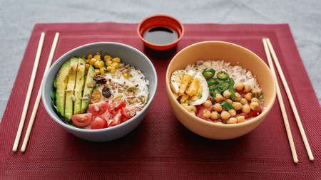 Close up of two bowls with sliced vegetables and rice served on napkin