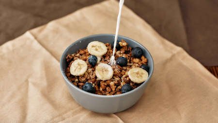 Pouring, adding milk to homemade granola in a plate with nuts, honey, blueberries and banana, served on napkin