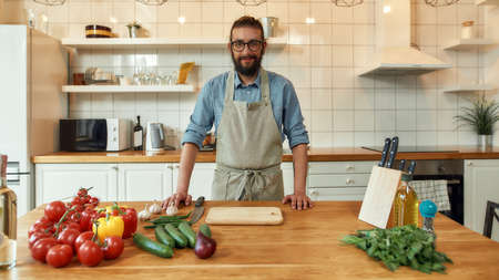 Young man, Italian cook in apron smiling at camera while preparing healthy meal with vegetables in the kitchen. Cooking at home concept