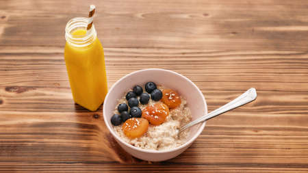 Healthy breakfast ideas, Oatmeal bowl with fresh blueberries, dried apricots and smoothie in the bottle on the wooden table 免版税图像 - 155309912