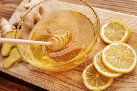 Close up of fresh ginger, lemon, honey in a bowl with dipper on the wooden board, Preparation of cold and flu remedy cure drink