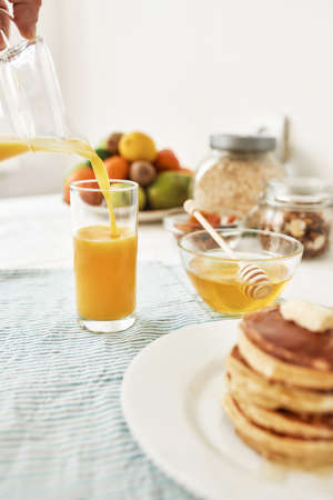 The process of pouring orange juice in the glass, Honey in a bowl with dipper, pancakes and various fruits served for breakfast on the table