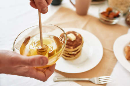 Close up of hands holding a bowl with honey, A stack of sweet tasty pancakes on the table, Process of preparing breakfast 免版税图像