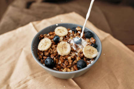 Pouring, adding milk to homemade granola in a plate with nuts, honey, blueberries and banana, served on napkin 免版税图像 - 155341477