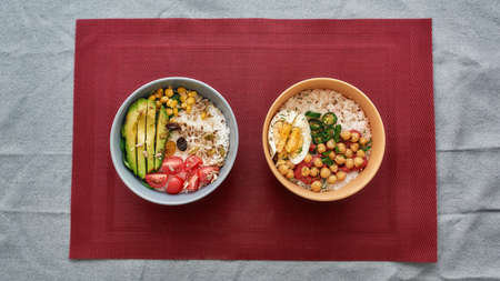 Top view of two bowls with sliced vegetables and rice served on napkin 免版税图像 - 155341199