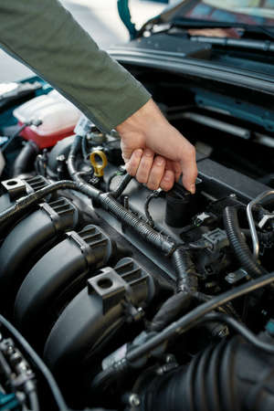 Close up of man hand checking the engine of a broken car