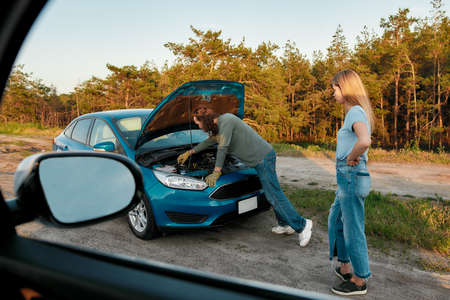 Girl having troubles with her auto, Man decided to help her, he is looking under the hood of broken car and trying to repair it, View from another car window Stock fotó