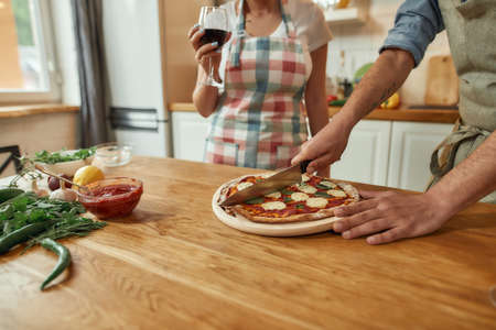 Cropped shot of man, cook cutting hot freshly baked pizza on the table while his girlfriend drinking wine. Couple making pizza together. Hobby, lifestyle 免版税图像 - 155450549