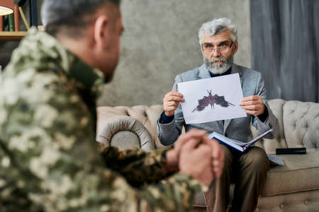 Mature psychologist holding picture with ink stain, Rorschach Inkblot in front of military man during therapy session. Soldier suffering from depression, psychological trauma. PTSD concept