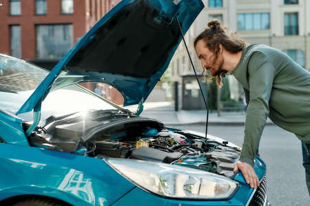 Young man looking focused, examining his broken car with open hood while standing on the city street