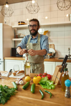 Young man, Italian cook looking cheerful while opening a bottle of white wine with a corkscrew in the kitchen