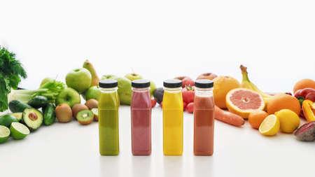 白い背景に分離された様々なカラフルな果物や野菜と健康的なデトックスジュースとスムージーのボトルの組成