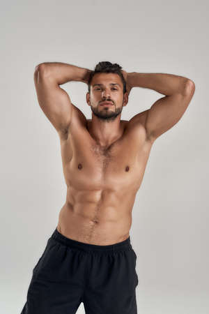 Young muscular caucasian man looking at camera and showing his torso while posing shirtless isolated over grey background