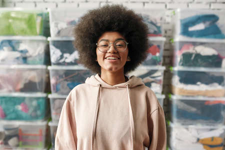 Portrait of happy african american girl smiling at camera while posing in front of boxes full of clothes, Young volunteer working for a charity, donating apparel to needy people