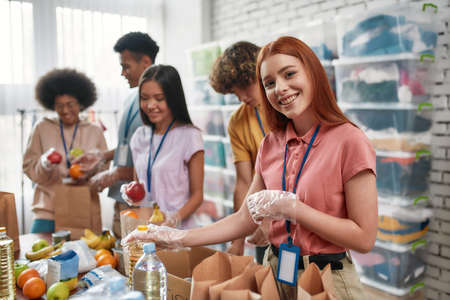 Young female volunteer smiling at camera while packing food and drinks donation into paper bags and box, Small group of people working in charitable foundation