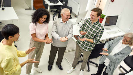 Group of diverse employees applauding while standing together in the office, Aged woman and man, senior interns having first day at work Stock fotó