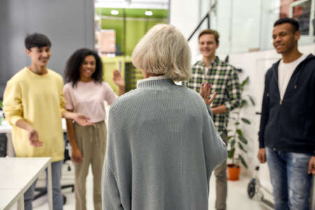 Cheerful young team greeting new employee, Back view of aged woman, senior intern waving at her colleagues in the modern office Standard-Bild