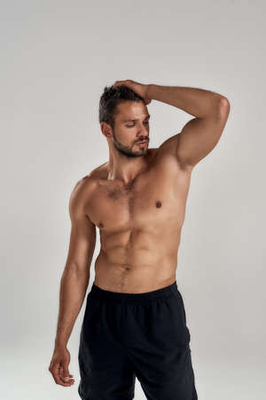 Perfect body. Young muscular caucasian man showing his torso while posing shirtless isolated over grey background