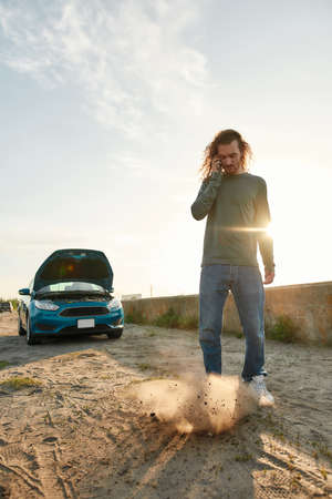 Full length shot of young man talking on the phone with car service, assistance or tow truck while standing near his broken car with open hood